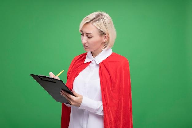 Geconcentreerde blonde superheld vrouw van middelbare leeftijd in rode cape schrijven met potlood op klembord geïsoleerd op groene muur met kopie ruimte