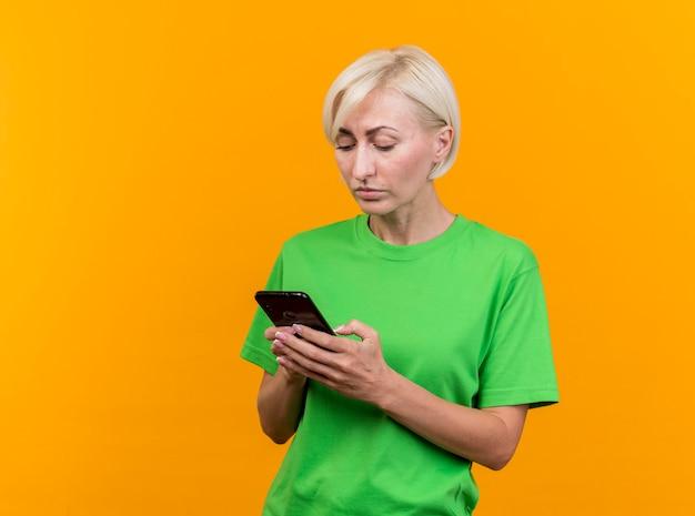 Geconcentreerde blonde vrouw die op middelbare leeftijd haar mobiele telefoon met behulp van die op gele muur wordt geïsoleerd