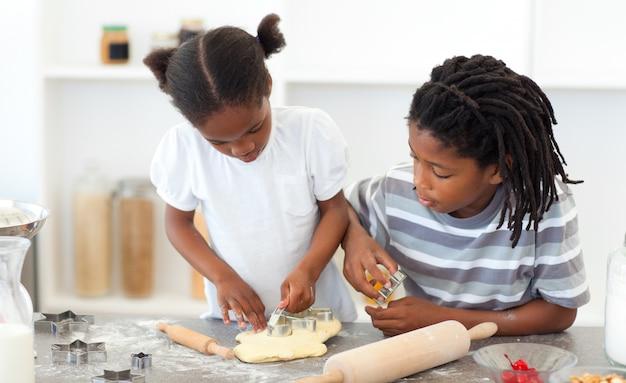 Geconcentreerde broers en zussen voor het koken van koekjes