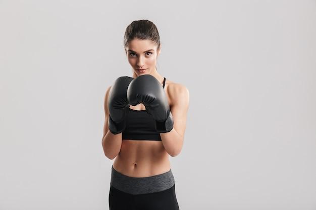 Geconcentreerde brunette sportvrouw training in bokshandschoenen over grijze muur
