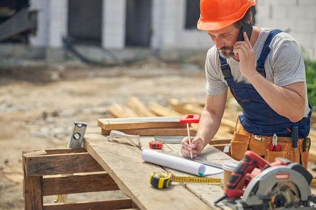 Geconcentreerde burgerlijk ingenieur met een mobiele telefoon in zijn hand leunend over een houten tafel