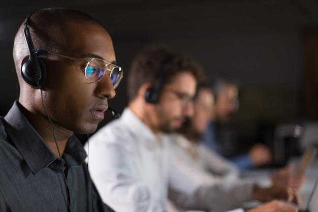 Geconcentreerde call center operator communiceert met de klant