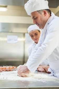 Geconcentreerde chef-kok die deeg kneden
