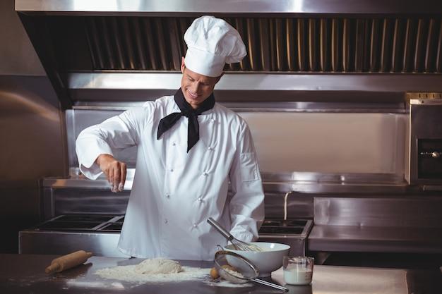 Geconcentreerde chef-kok die een cake voorbereidt