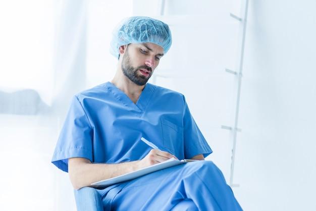 Geconcentreerde chirurg die op klembord schrijft