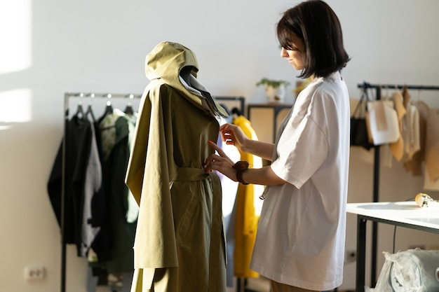 Geconcentreerde designer fit jas op mannequin in workshop ontwerpstudio atelier eigenaar naaien van kleding