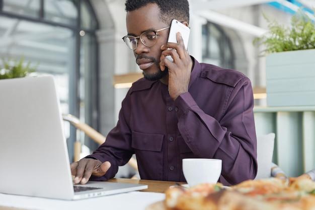 Geconcentreerde donkere man in formele kleding kijkt zelfverzekerd in laptop, heeft ernstige uitdrukking