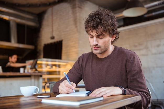Geconcentreerde, doordachte knappe, aantrekkelijke, krullende man in een bruin sweetshirt die zijn schema plant terwijl hij in café zit