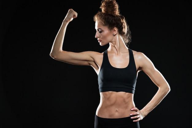 Geconcentreerde ernstige jonge sport dame met haar biceps.