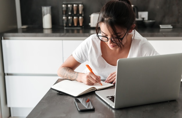 Geconcentreerde ernstige jonge vrouw die laptop computer het schrijven nota's met behulp van.