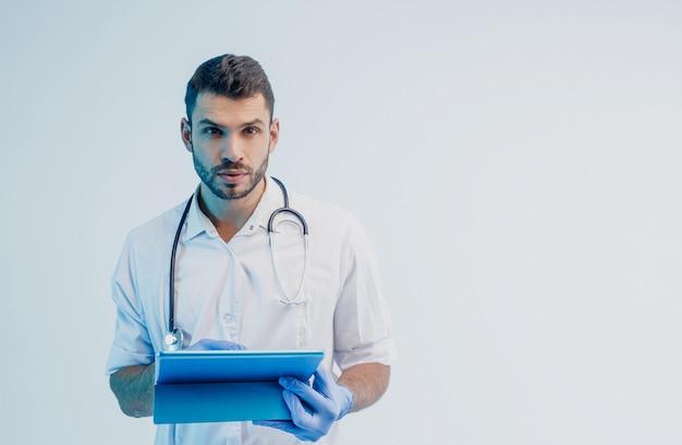 Geconcentreerde europese mannelijke arts met digitale tablet. jonge, bebaarde man met een stethoscoop die een witte jas draagt met latexhandschoenen. grijze achtergrond met turkoois licht. studio opname. ruimte kopiëren.