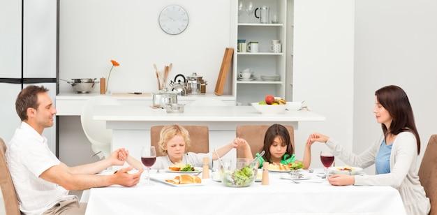 Geconcentreerde familie die vóór het hebben van de lunch bidt