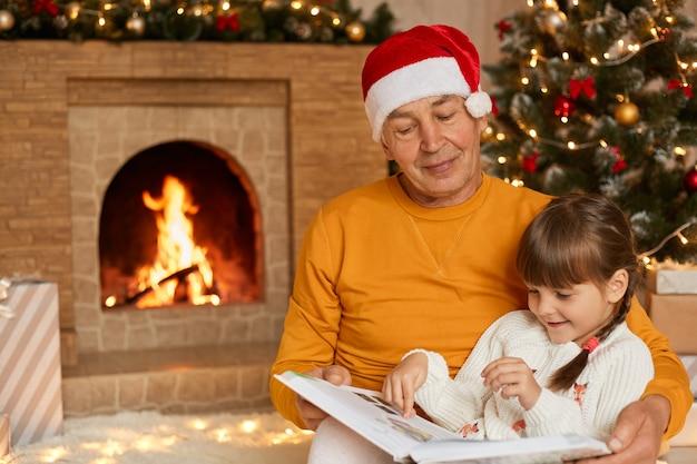 Geconcentreerde familie zittend op de vloer in de woonkamer en sprookje lezen en kijken naar foto's, tijd samen doorbrengen op kerstavond, senior man met kerstman hoed, opa en kleindochter.
