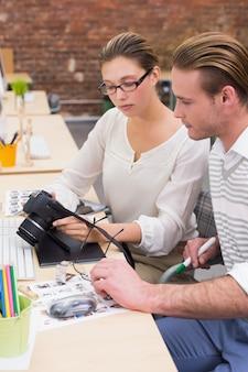 Geconcentreerde fotoredacteurs die camera in bureau bekijken