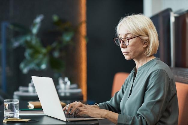 Geconcentreerde freelance senior vrouw met kort blond haar die aan tafel zit en laptop gebruikt terwijl ze werkt aan website-inhoud in café