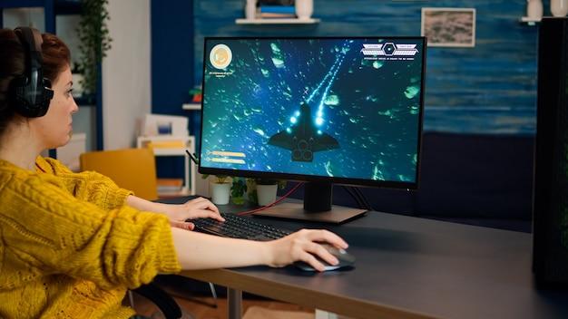 Geconcentreerde gamer die first-person space shooter online videogame speelt op een krachtige pc die thuis vrije tijd doorbrengt. esport cyber optreden tijdens gametoernooi