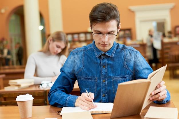 Geconcentreerde geek die nota's in bibliotheek neemt