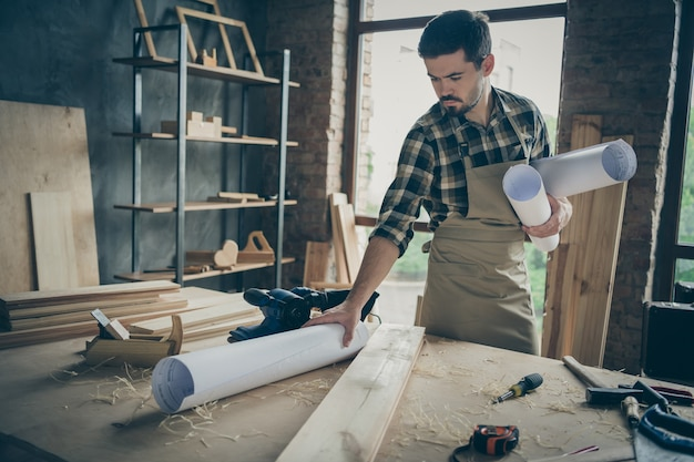 Geconcentreerde gefocuste serieuze man met opgerolde blauwdrukken met documenten op canvas geplaatst met tal van gereedschappen