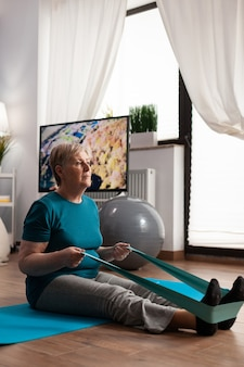 Geconcentreerde gepensioneerde die sportkleding draagt die op yogamat zit die benenspier uitrekt gebruikend fitness elastische band tijdens aerobicstraining die spierweerstand uitoefent