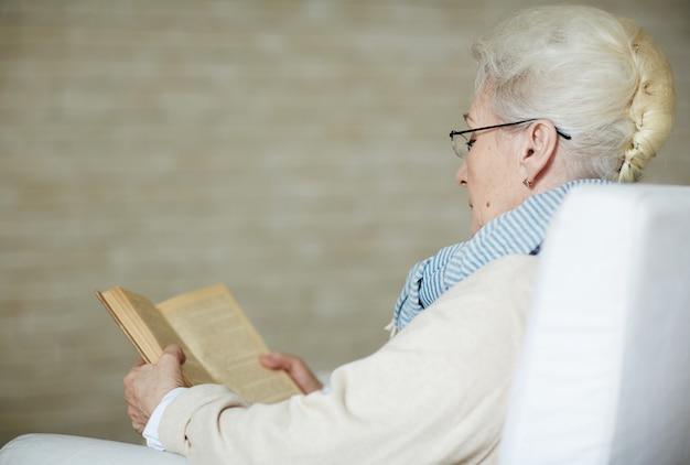 Geconcentreerde gepensioneerde vrouw die oud boek leest