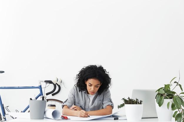 Geconcentreerde hardwerkende geschoolde jonge vrouwelijke ontwerper blauwdruk tekenen