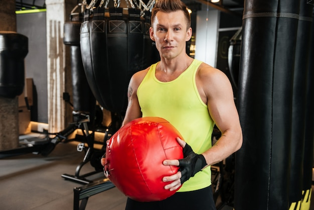 Geconcentreerde het gewichtsbal van de sportmanholding terwijl status bij de gymnastiek