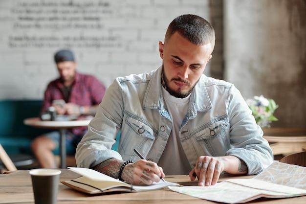 Geconcentreerde hipster man met baard zittend aan tafel in een modern café en papieren kaart bekijken terwijl hij aantekeningen maakt over de reis
