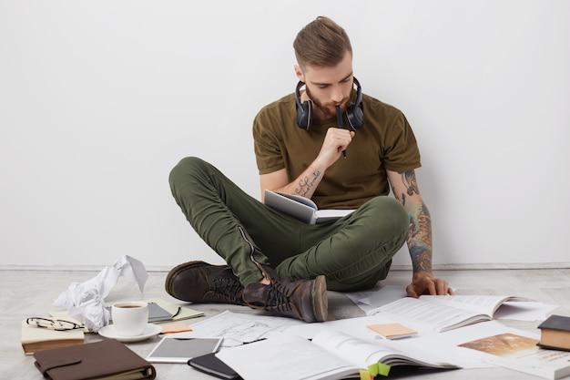 Geconcentreerde hipster man met tatoeages, gekruiste benen op de vloer zit, boeken leest en notities schrijft