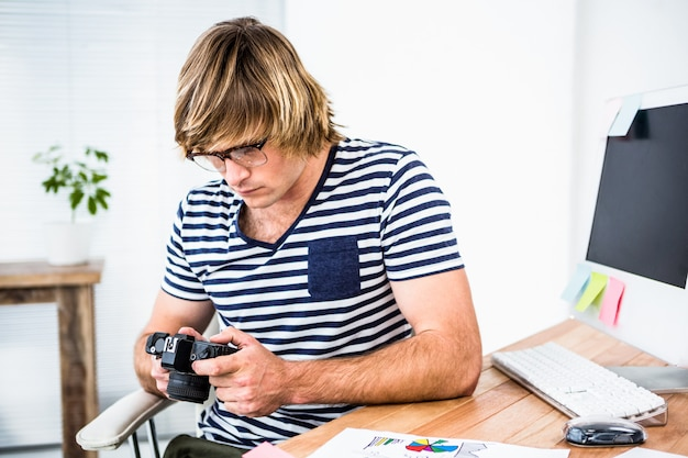 Geconcentreerde hipster zakenman die foto op camera in zijn bureau controleren