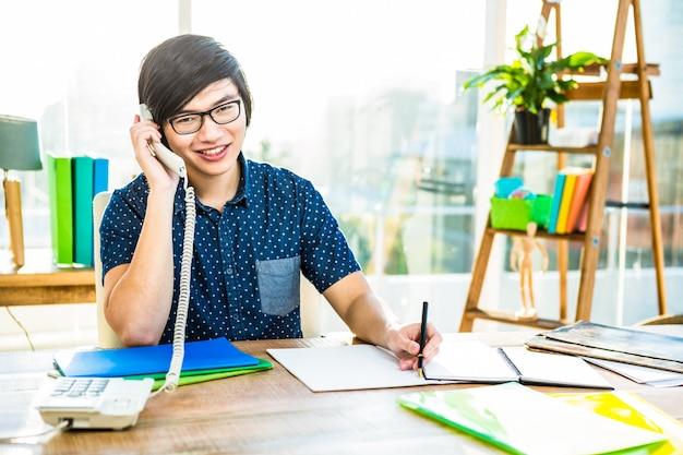 Geconcentreerde hipster zakenman die in bureau schrijft
