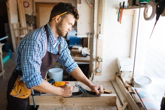 Geconcentreerde houtbewerker in werkplaats