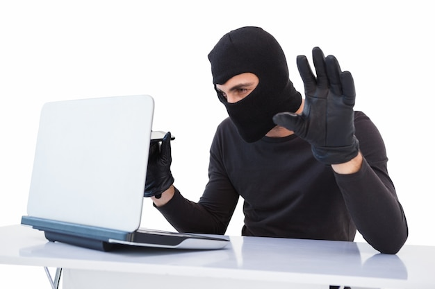 Geconcentreerde inbreker die laptop binnendringen in een beveiligd computersysteem