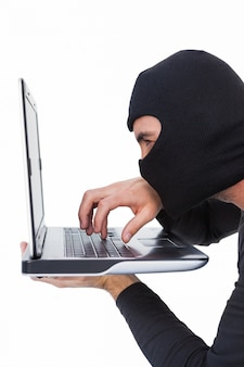 Geconcentreerde inbreker met bivakmuts die op laptop typen