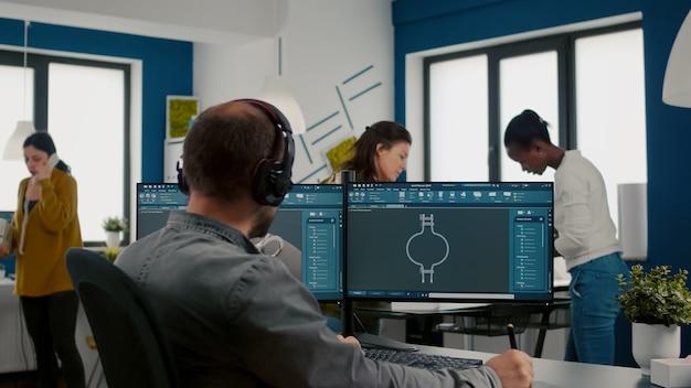 Geconcentreerde ingenieur die een koptelefoon opzet die werkt met een technisch cad-programma dat het prototype van de versnellingen controleert...