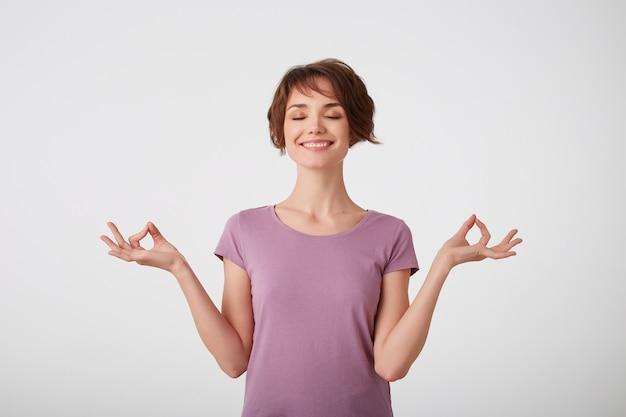Geconcentreerde jonge aantrekkelijke jonge kortharige dame in leeg t-shirt, houdt de handen in oke gebaar, mediteert binnen, heeft gesloten ogen, probeert te ontspannen, geïsoleerd op een witte muur.