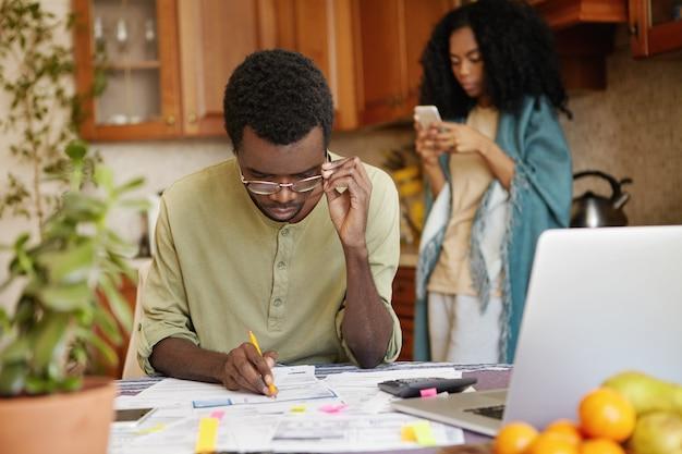 Geconcentreerde jonge afrikaanse man die papieren invult, zijn bril aanpast terwijl hij de financiën beheert