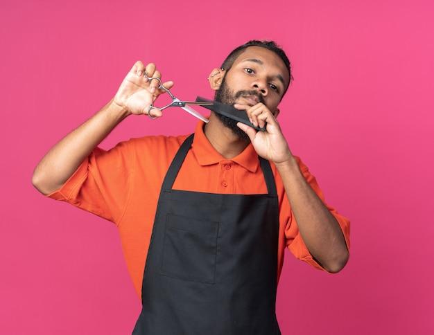 Geconcentreerde jonge afro-amerikaanse mannelijke kapper die een uniform draagt en er recht uitziet met een schaar en een kam die zijn eigen baard snijdt
