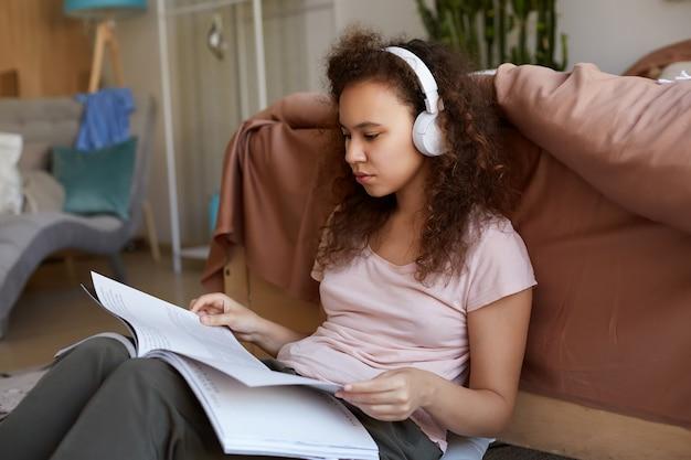 Geconcentreerde jonge afro-amerikaanse vrouw met krullend haar aanbrengen in de kamer, gekleed in pyjama's, zijn favoriete muziek in koptelefoon luisteren, nieuw tijdschrift lezen.