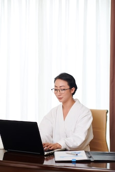 Geconcentreerde jonge aziatische zakenvrouw in badjas en bril zittend aan tafel en typen op schoot...