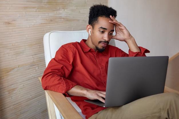 Geconcentreerde jonge bebaarde donkere man met kort kapsel houden opgeheven hand op zijn hoofd tijdens het controleren van de e-mailbox op zijn laptop, geïsoleerd op interieur