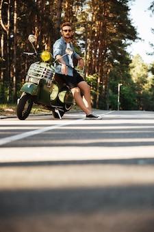 Geconcentreerde jonge bebaarde man die in de buurt van scooter