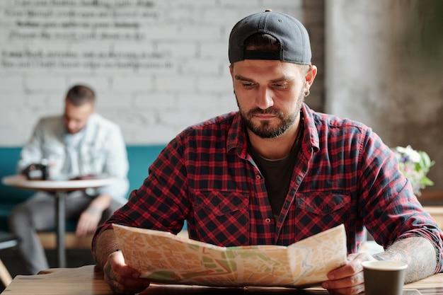 Geconcentreerde jonge bebaarde man in bal glb aan tafel zitten en met behulp van papieren kaart in café