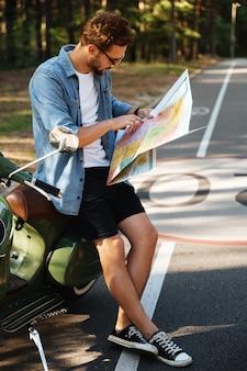 Geconcentreerde jonge bebaarde man in de buurt van scooter kijken naar kaart