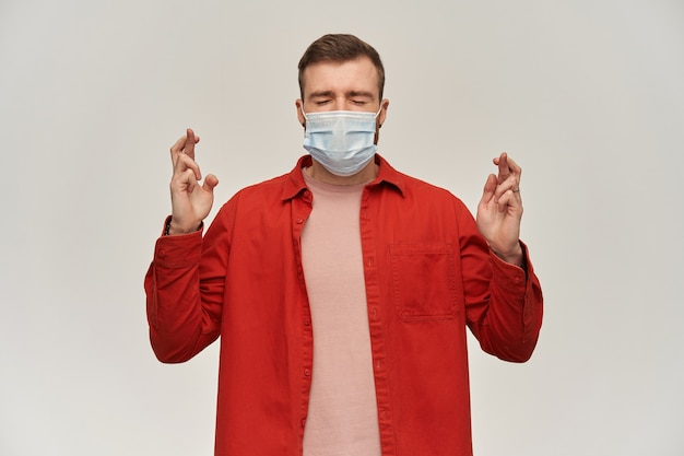 Geconcentreerde jonge bebaarde man in rood shirt en virus beschermend masker op gezicht tegen coronavirus houdt ogen gesloten en vingers gekruist over witte muur een wens doen