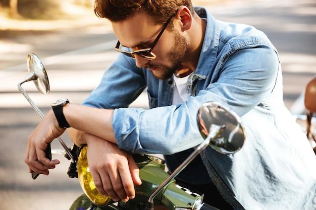 Geconcentreerde jonge bebaarde man zittend op scooter buitenshuis