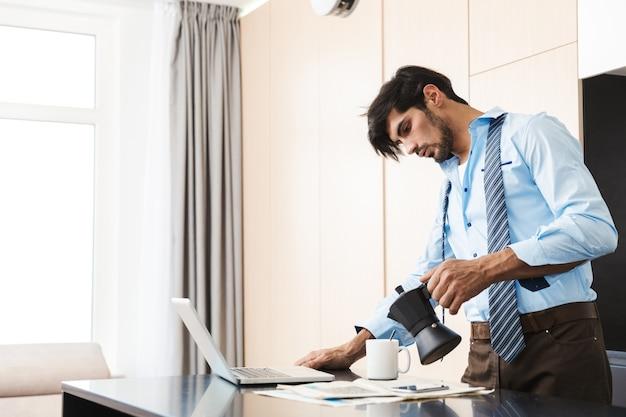 Geconcentreerde jonge bedrijfsmens bij de keuken die door mobiele telefoon spreekt.