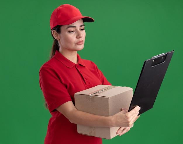 Geconcentreerde jonge bezorger in uniform en pet met kartonnen doos en klembord kijkend naar klembord