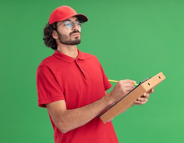 Geconcentreerde jonge blanke bezorger in rood uniform en pet met bril met pizzapakket schrijvend op klembord met potlood kijkend naar klembord
