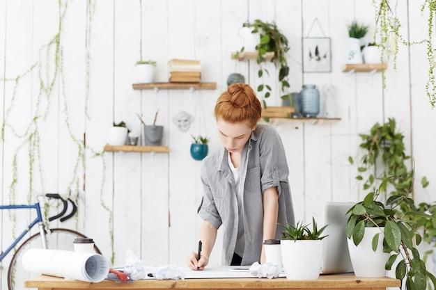 Geconcentreerde jonge blanke roodharige vrouw ingenieur met haarbroodje