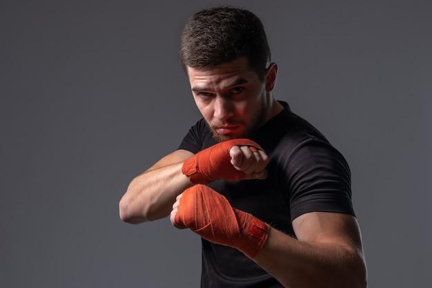 Geconcentreerde jonge bokser met handomslagen die een defensieve houding uitwerken